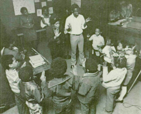 Yomi Moses, a Nigerian student at North Carolina Central University, leads children in singing their ABCs at a children's meeting of the Community Radio Workshop.  Moses also taught children his native Yoruban language at the CRW.